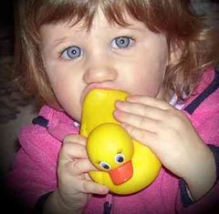Little girl chewing rubber duck